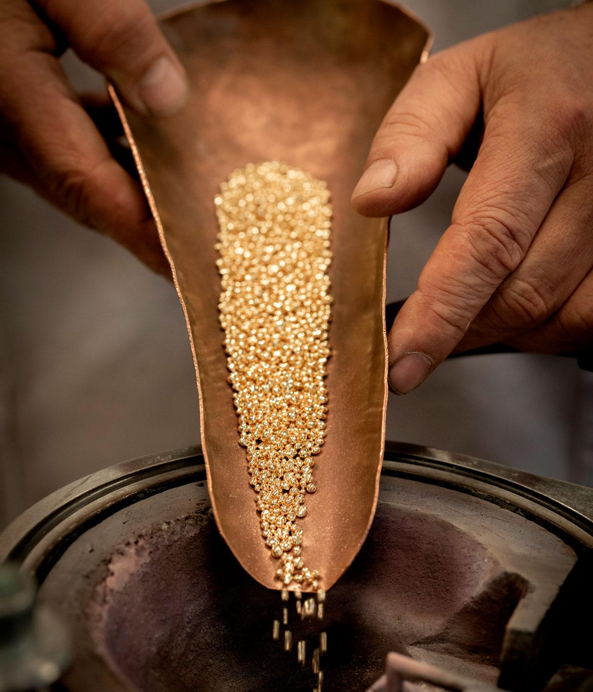 Gold beads being poured into a machine
