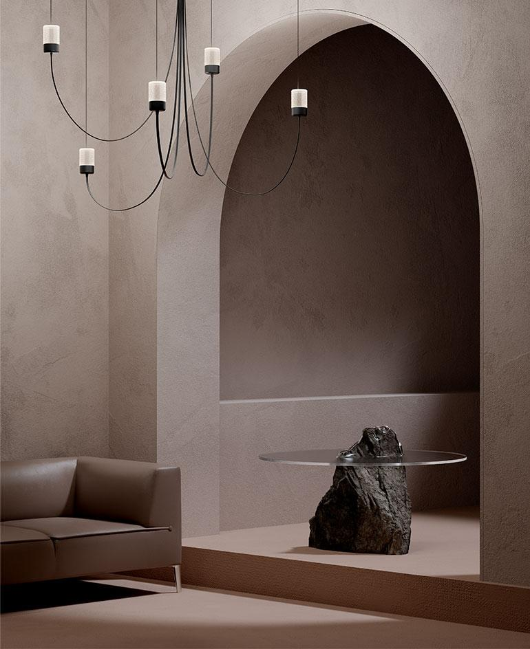 A render showing Paul Cocksedge's Gravity Chandelier for Moooi, a design featuring black curved arms hanging from the ceiling in a taupe-coloured room with an arched door, a side table made of stone and glass and a leather sofa