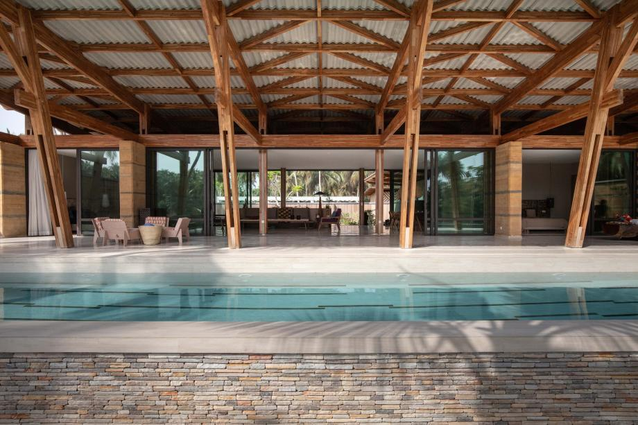 this retreat in the Ivory Coast features open plan interiors and large glazed facades that open up to nature and a swimming pool