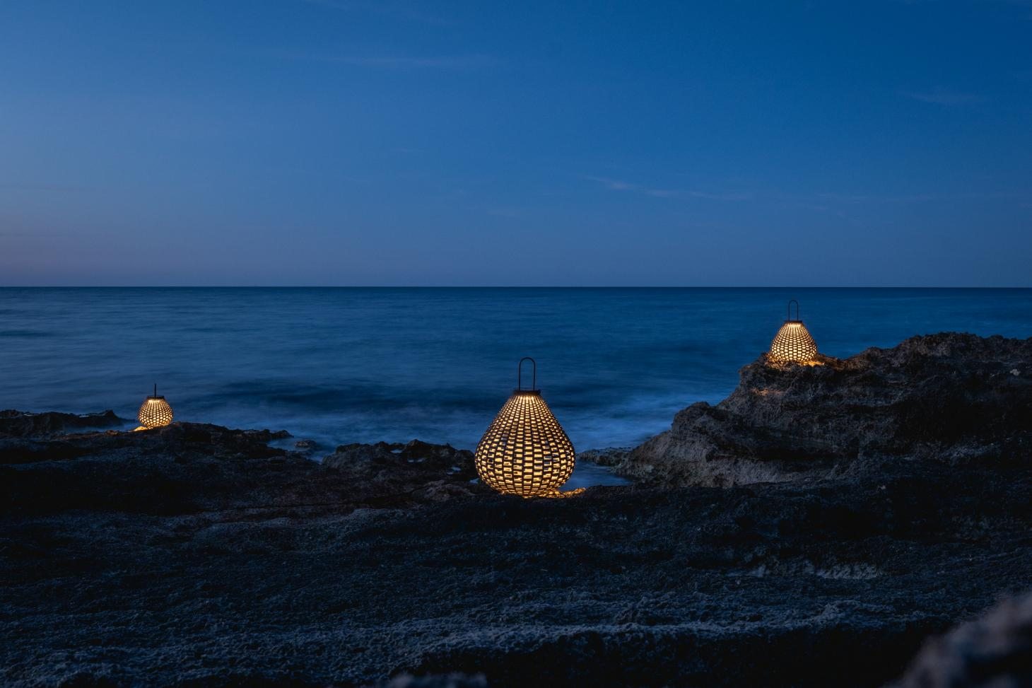 Three woven lanterns photographed on rocks by the sea at dusk