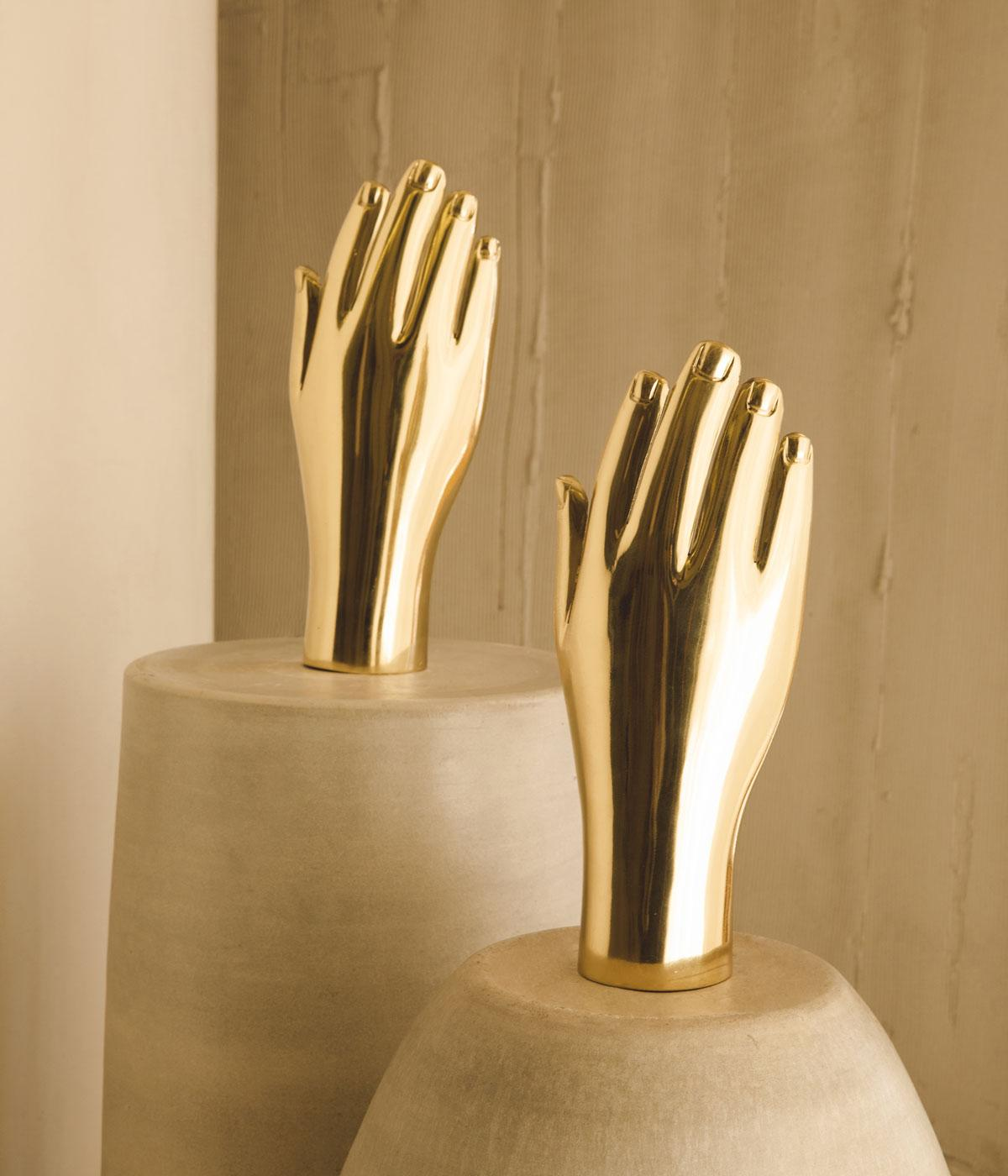 Hands in brass sat on round stone tables