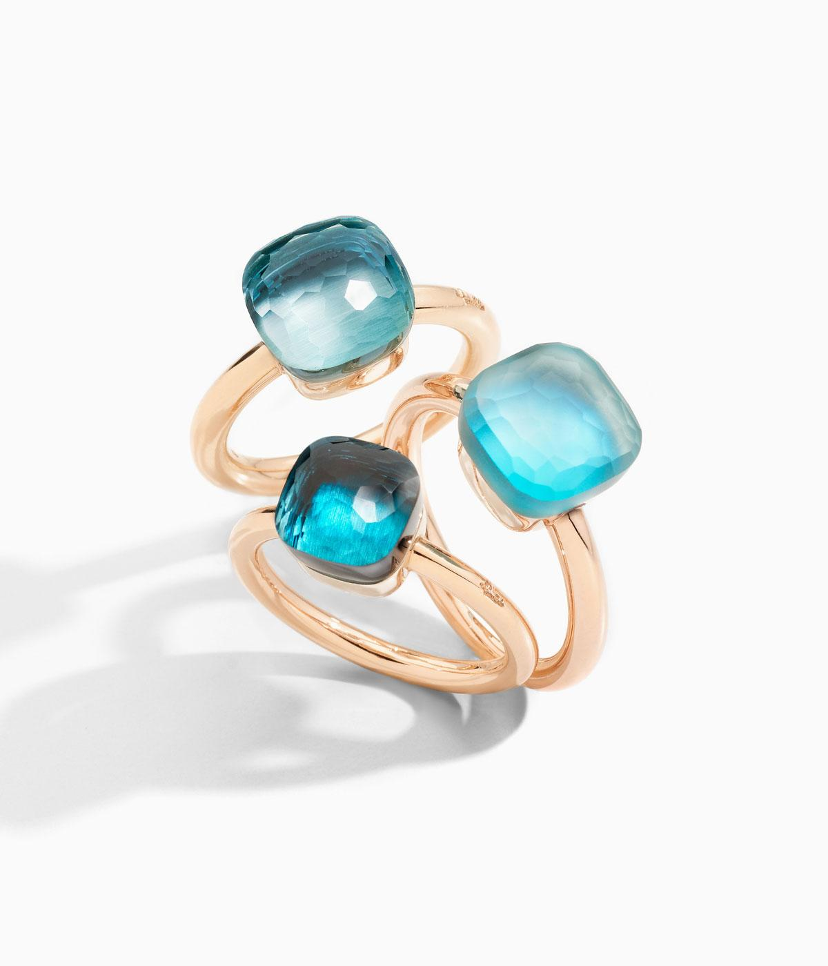Three gold rings with clear blue topaz on