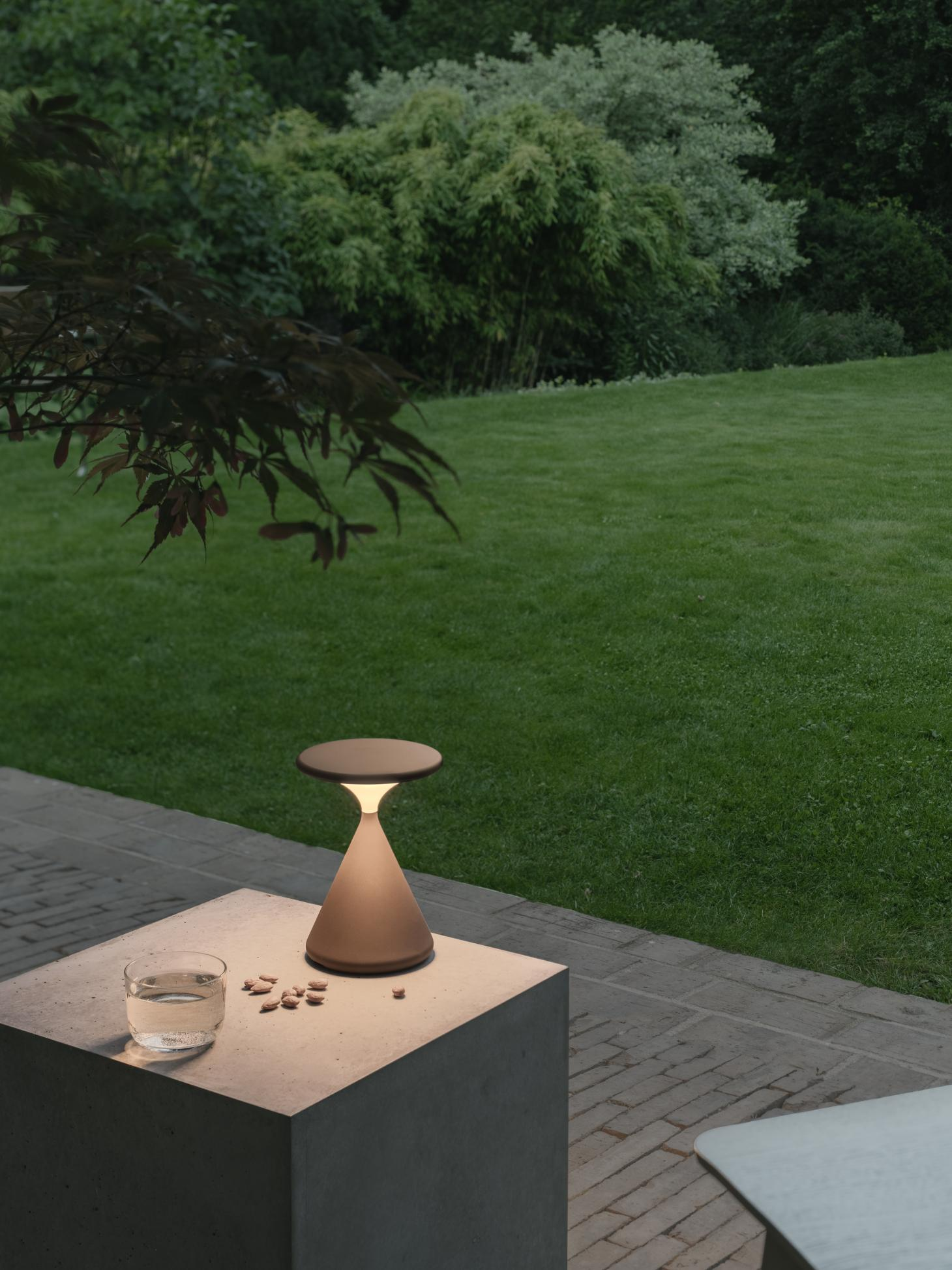 A garden photographed in the evening, with a concrete plinth holding a glass of water and an hourglass-shaped portable lamp by Tobias Grau