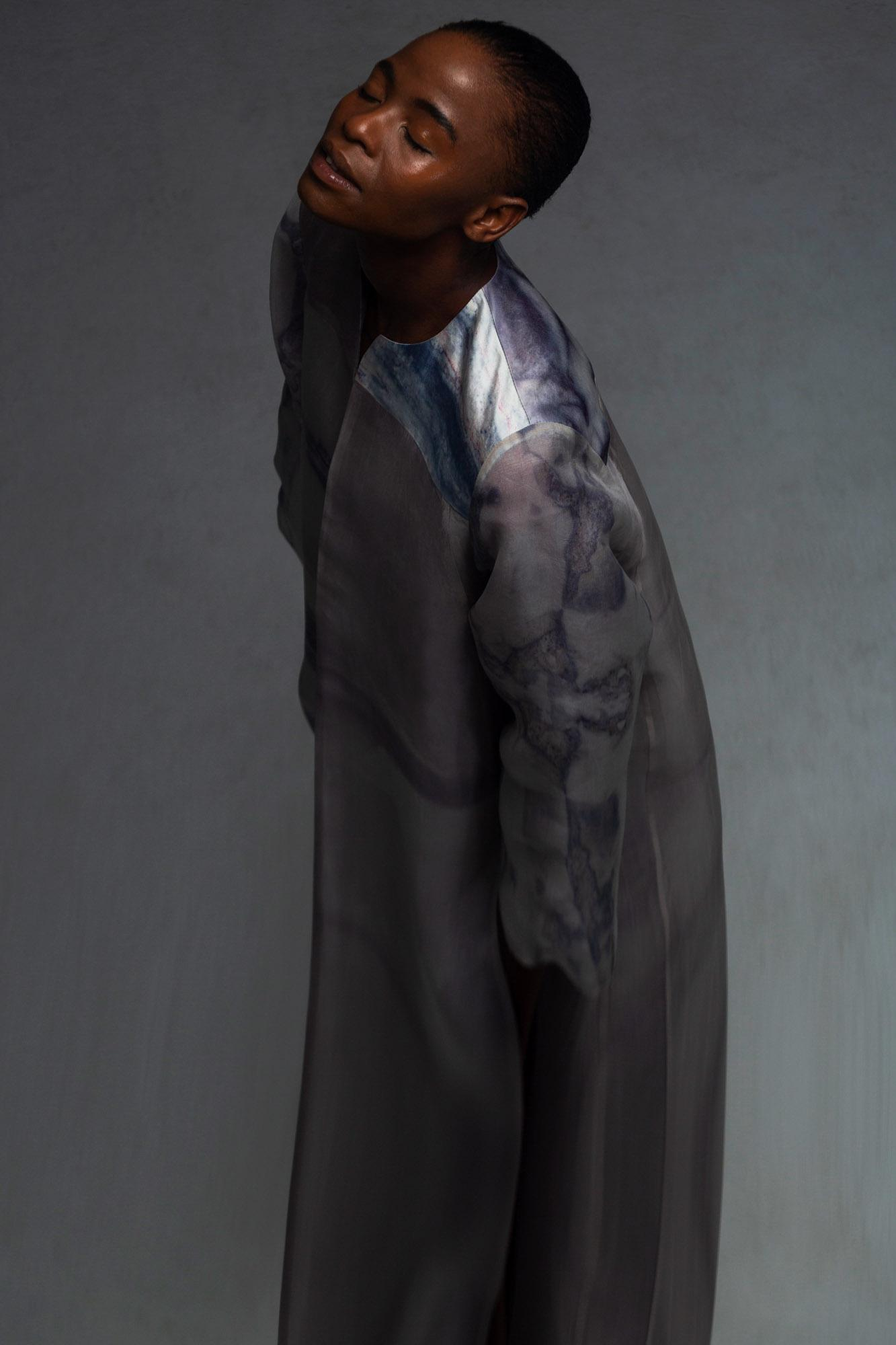 A model wearing a garment dyed with Coelicolor bacterial pigment extract, the result being a marbled effect of pink, purple and blue