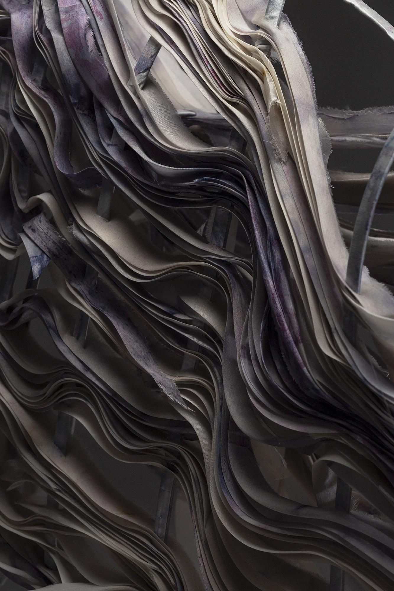A pile of silk pieces dyed in purple with Streptomyces Coelicolor