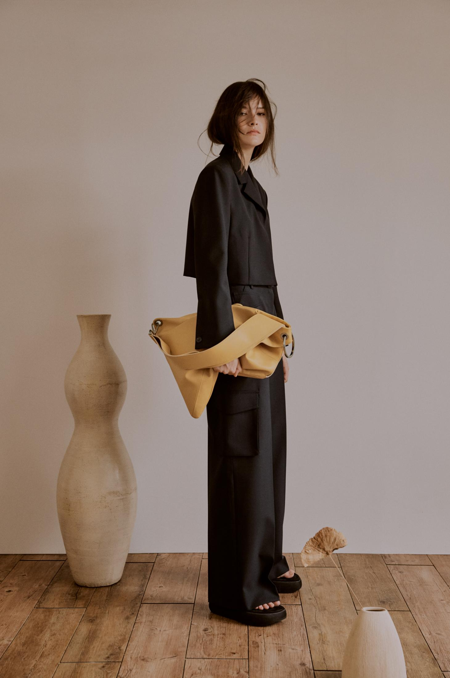 Woman stands holding a beige leather pouch