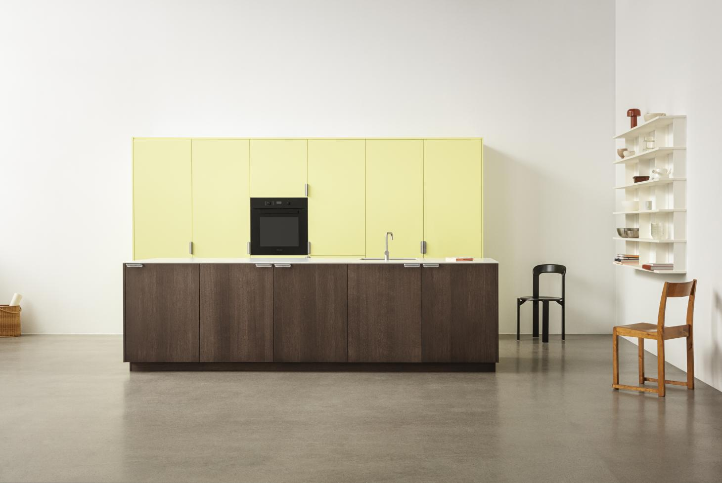 A large kitchen by Copenhagen based brand Reform, with tall canary yellow cupboards and a wooden island