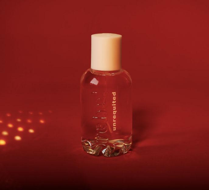 bel rebel's unrequited perfume in glass bottle against red background