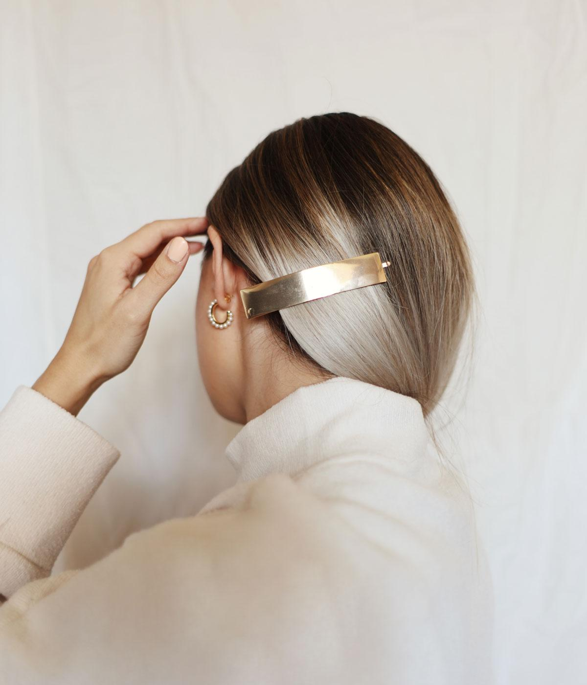 Back of a woman's head wearing a gold hair clip