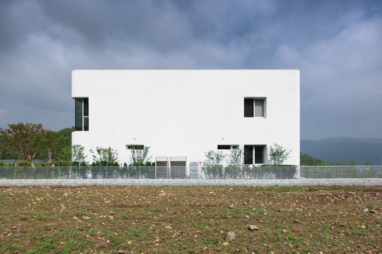 South Korean rounded house's minimalist white side facade