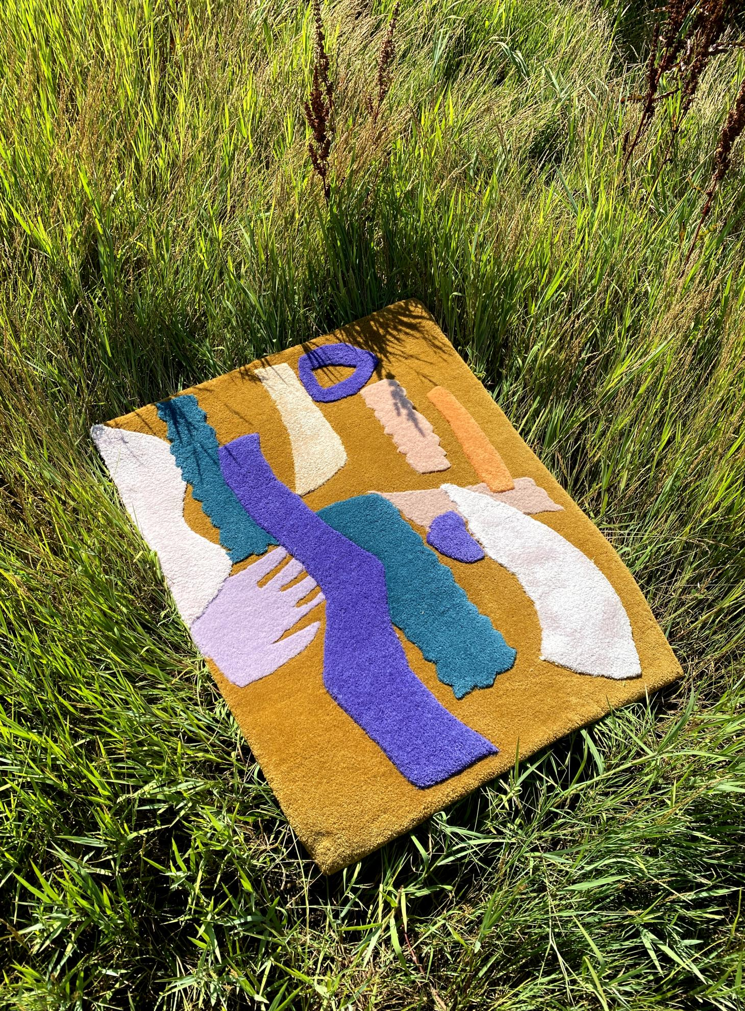 A colorful rug by Alex Proba laying on grass