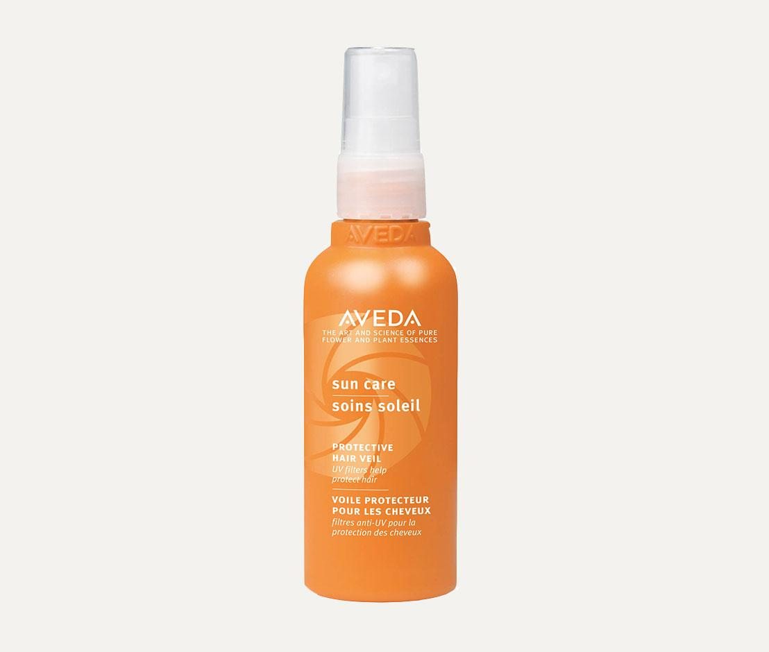 aveda sun care protective hair veil in orange bottle against grey background