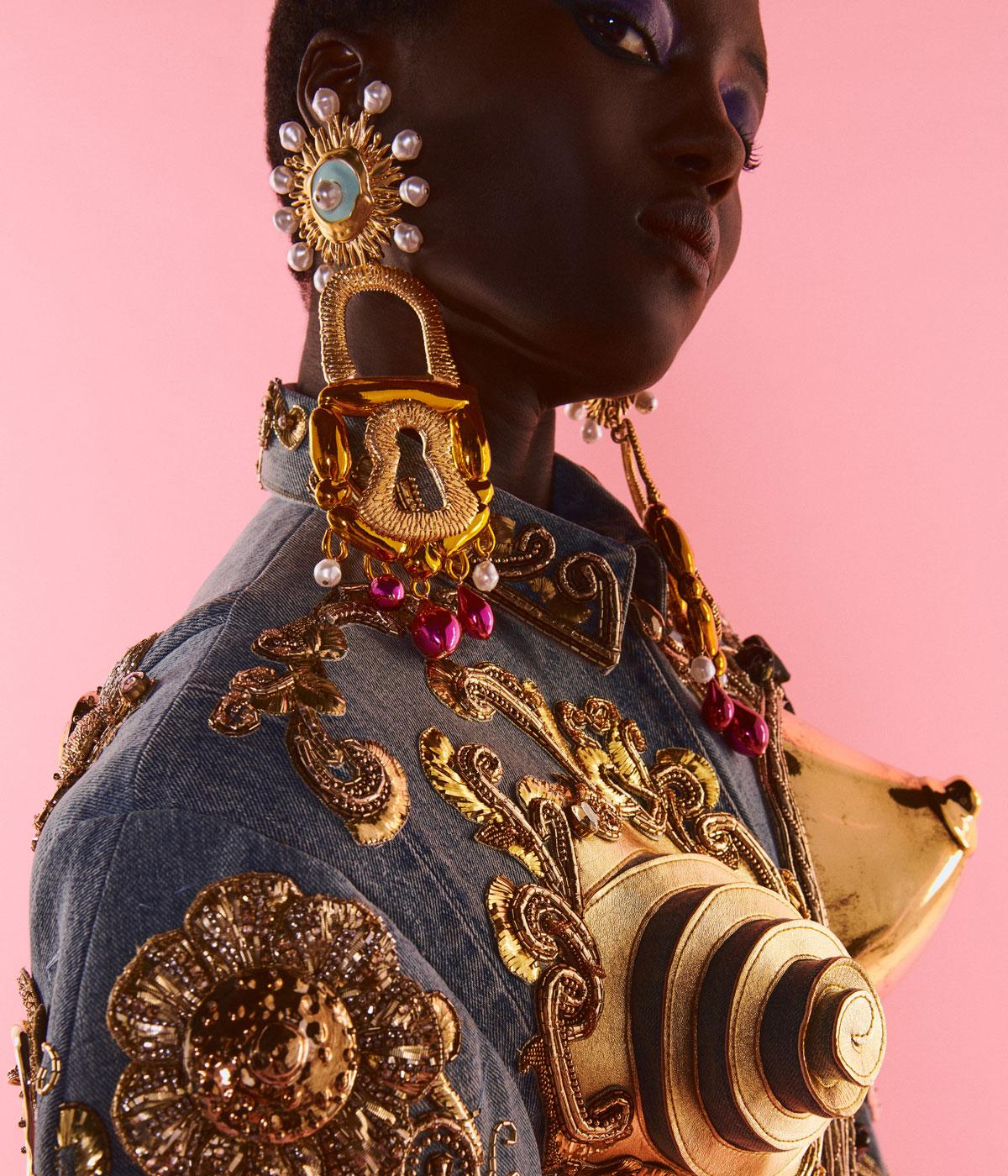 Woman wearing big gold earrings and gold breasts on her jacket