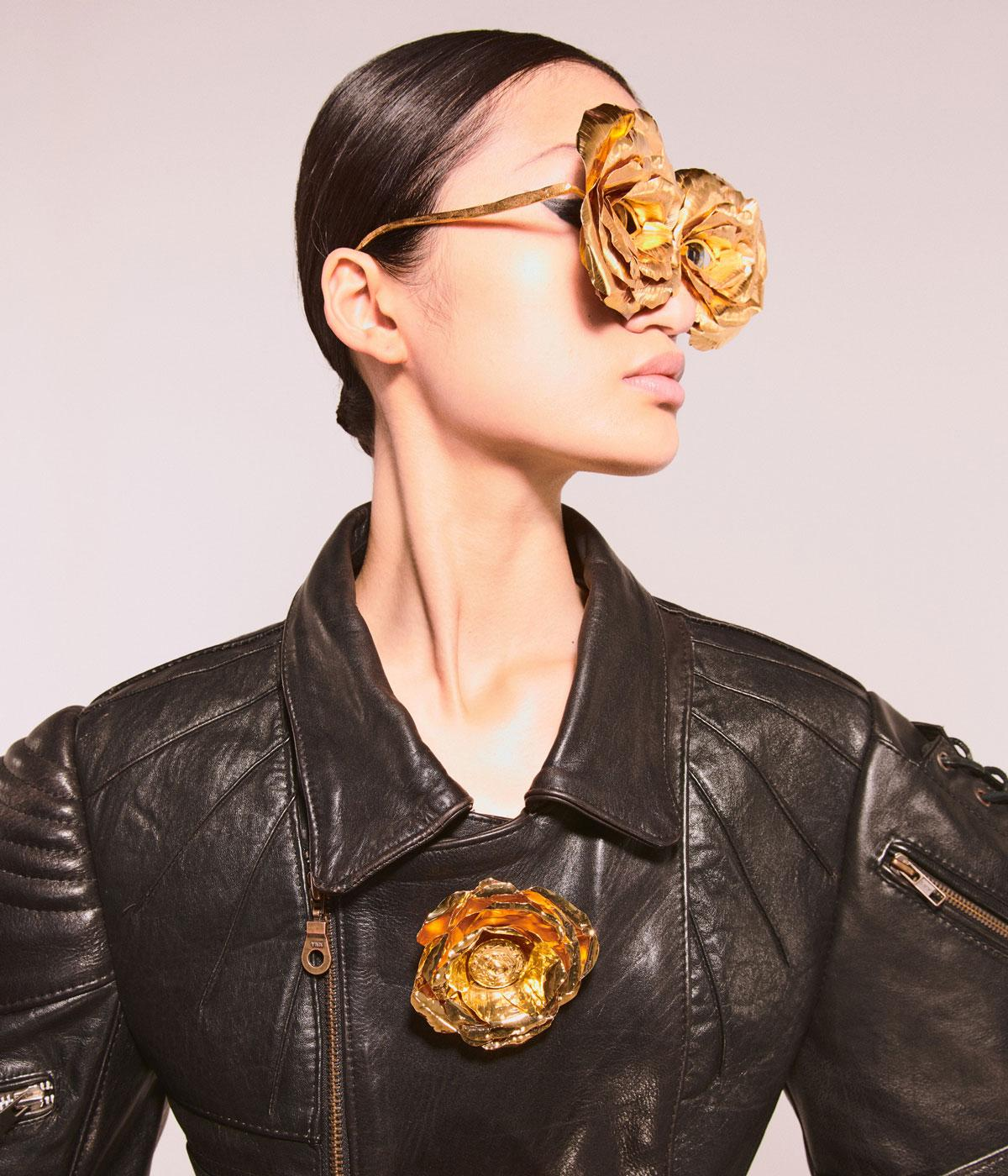 Woman wearing gold glasses with flower on them