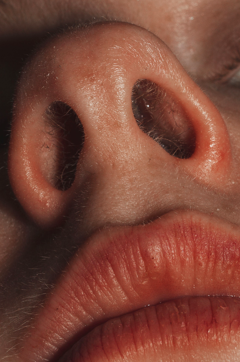 A photo taken from looking up at woman's nose and mouth in high definition