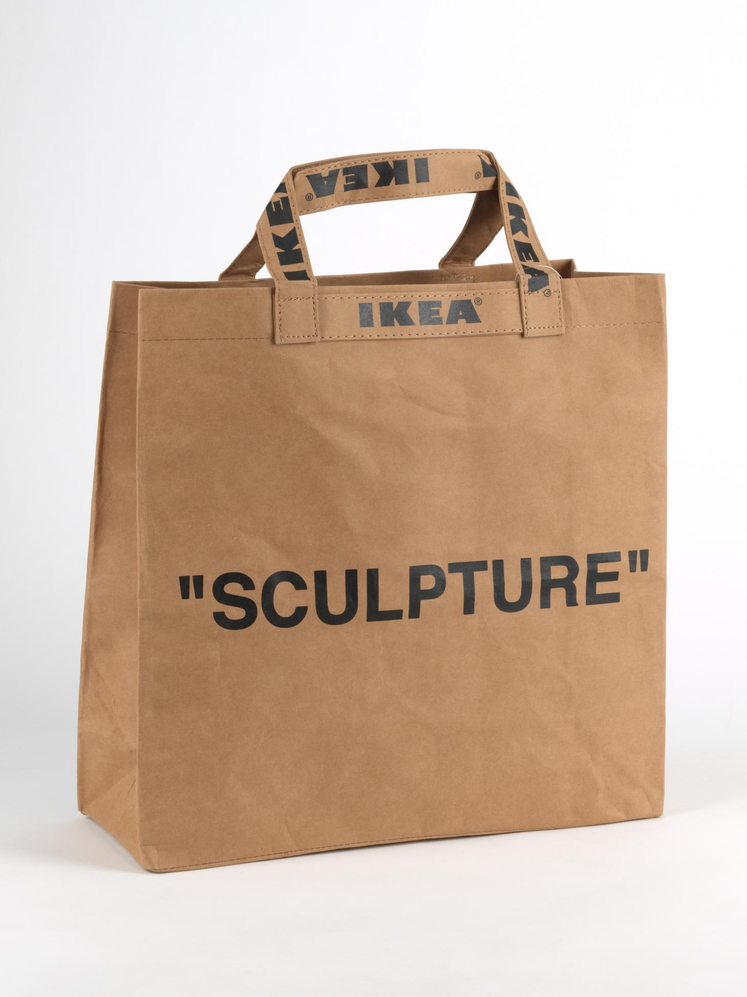 """A brown paper bag that says IKEA on the handles and """"sculpture"""" in black type on the front, created by Virgil Abloh"""