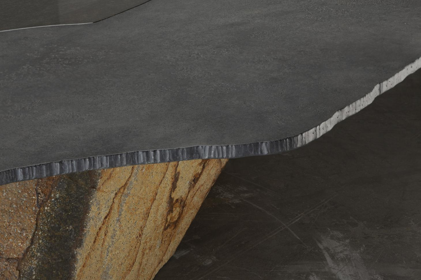 Detail of the materials used for the tables, including steel top and oxidised volcanic stone