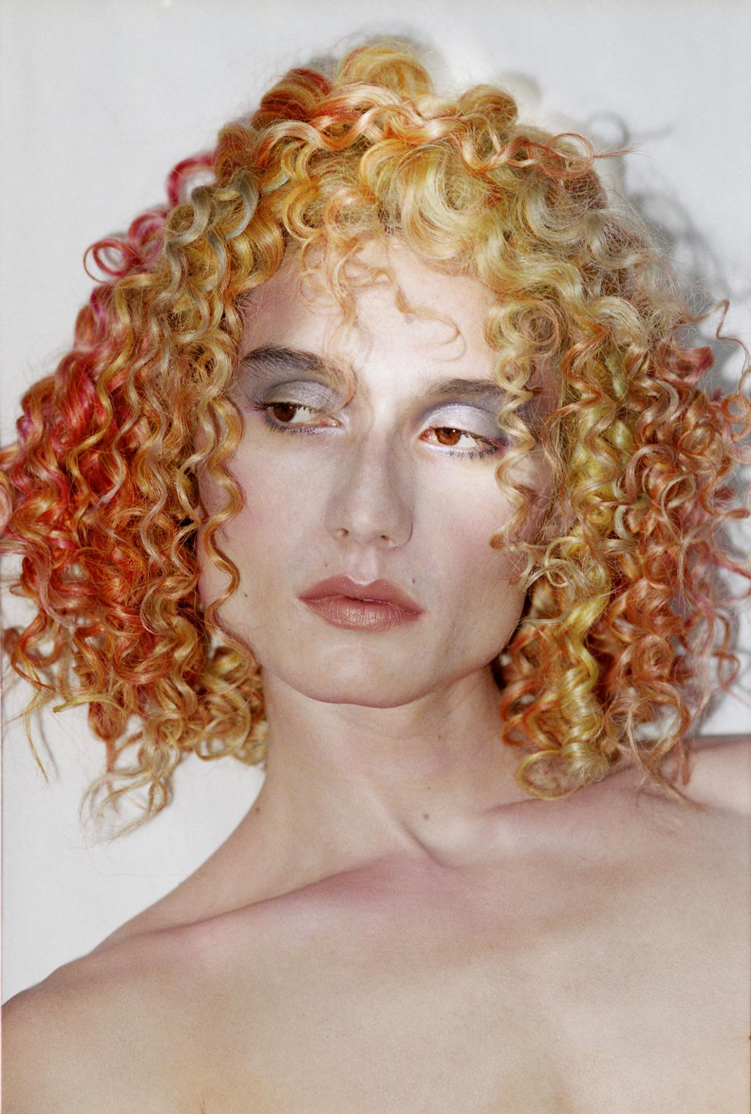 man wearing orange curly haired wig