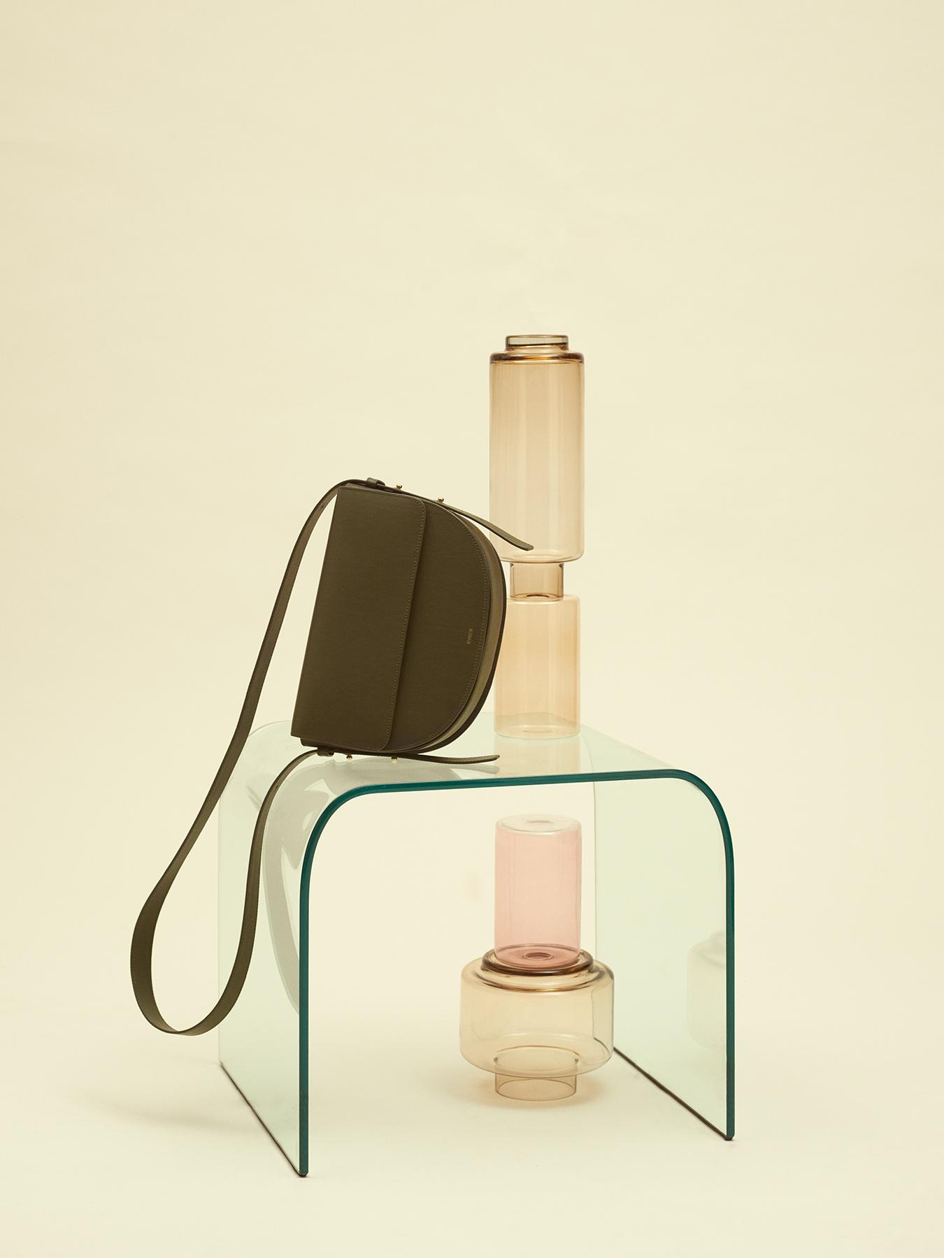 Green leather bag lies on a glass table