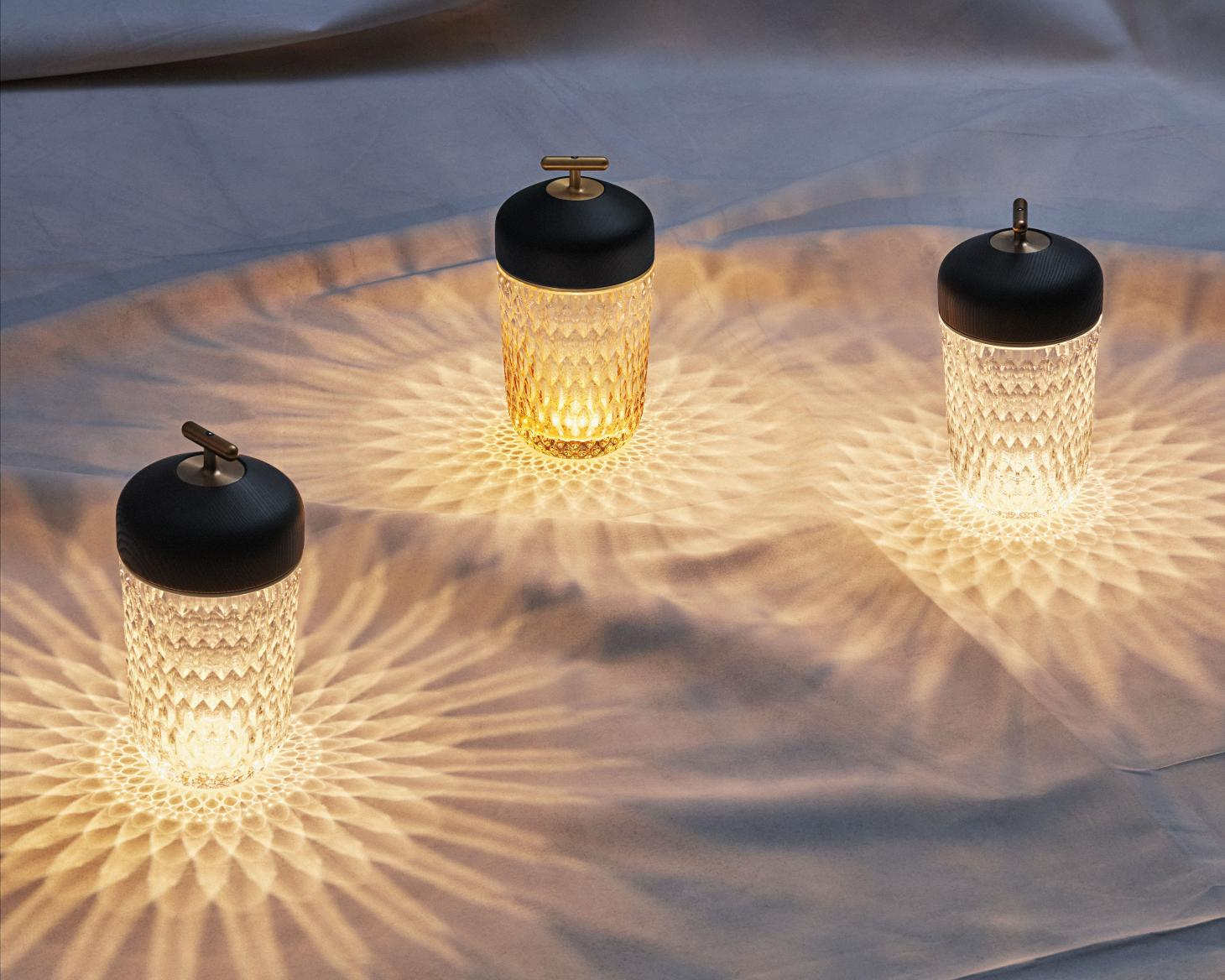 Three portable lamps in textured crystal, casting patterned lights and shadows on the surface below