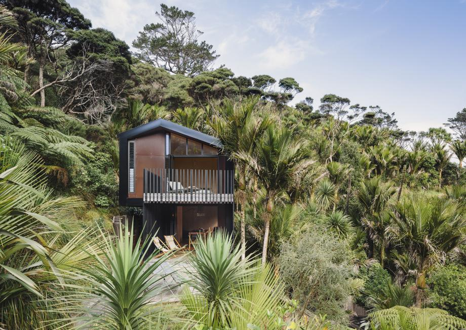 this New Zealand 'Bach' is perch on a hillside overlooking the sea