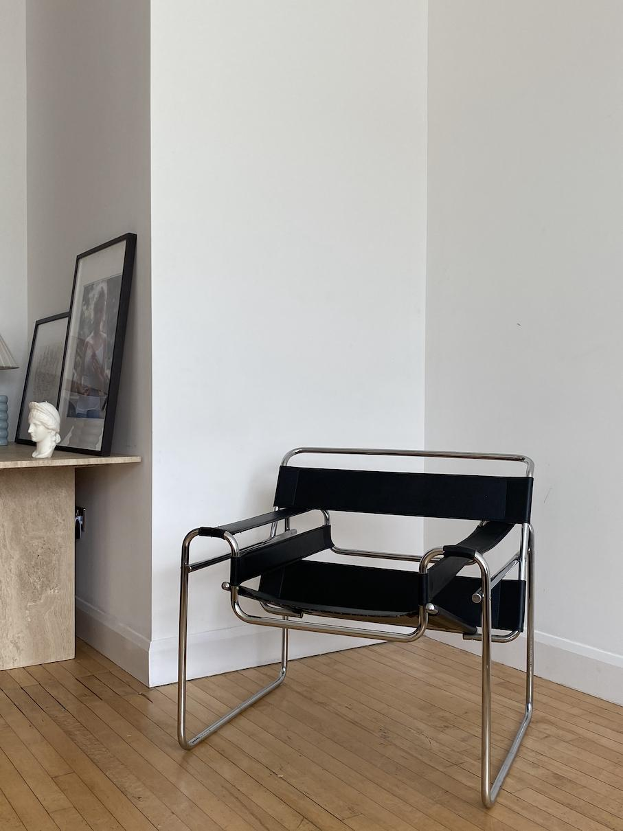 A chair with tubular steel frame and black leather seat and armrests