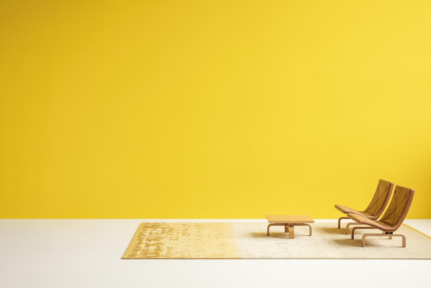 A wide room with bright yellow wall and white floor, with a pair of modernist chairs and coffee table placed onto a yellow and beige area rug by David Thulstrup