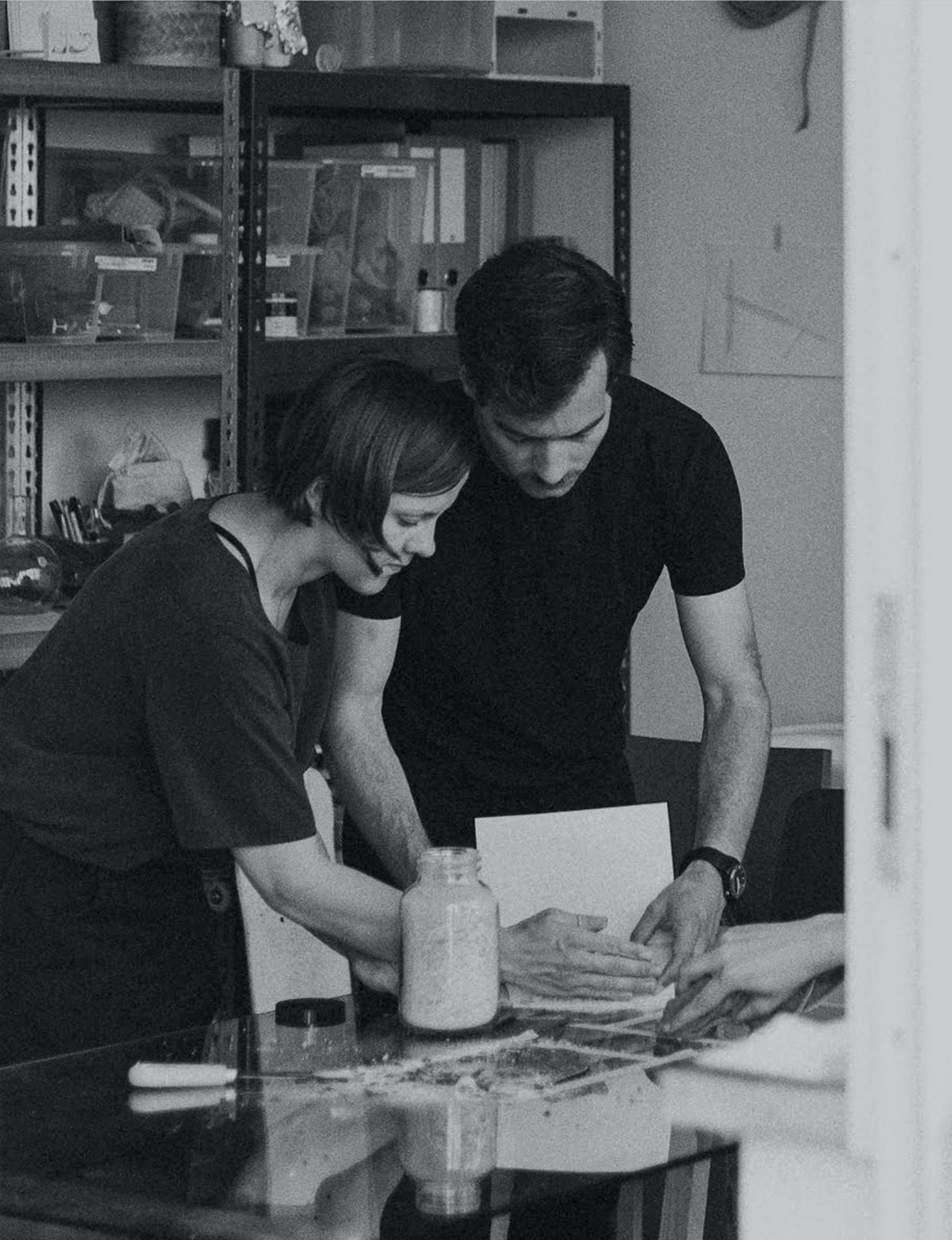 A black and white portrait of designers Archibald Godts and Theresa Bastek of Studio Plastique, working in their studio