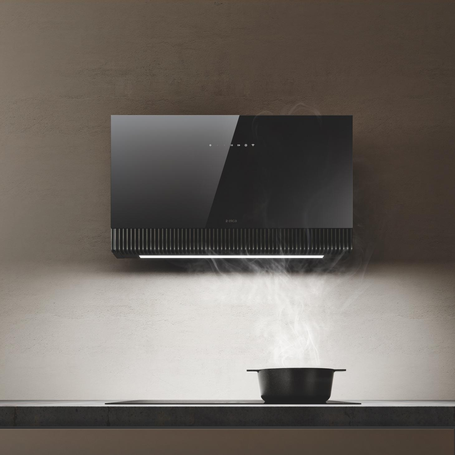 A black pot sitting under a high tech extractor hood by Elica