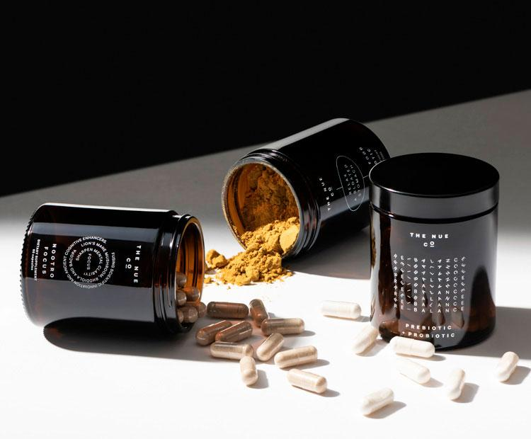 Nue Co powder and supplement pills in brown glass bottles on tabletop