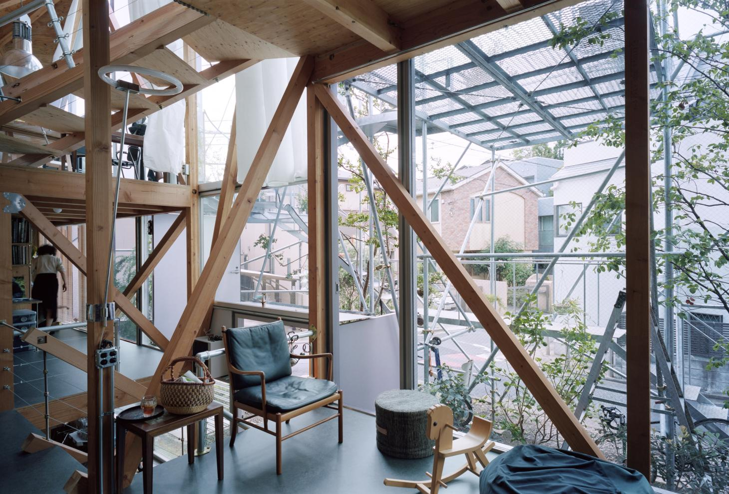 living space with large openings looking out at naked structure at Daita2019, a Japanese house