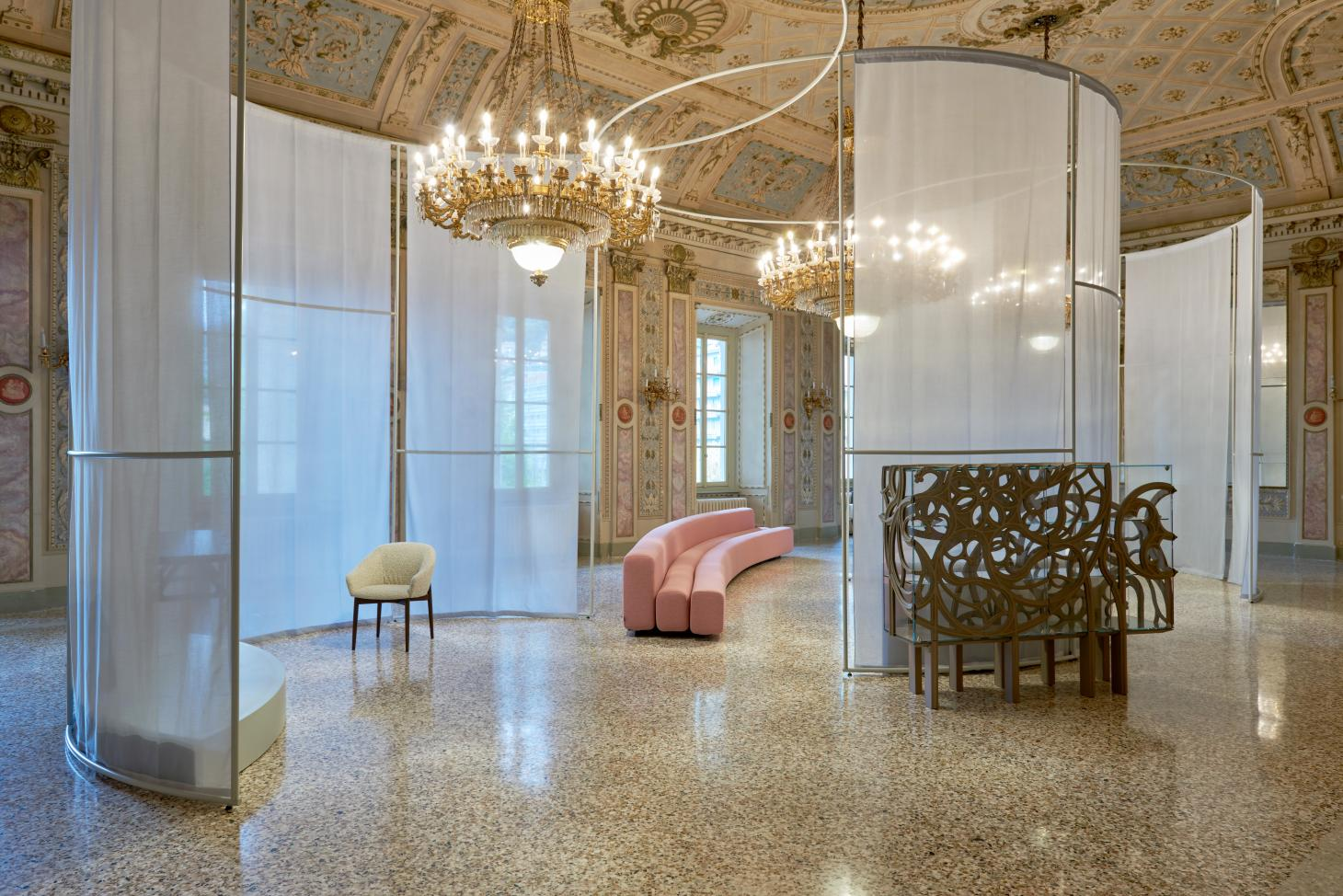 Interior of 18th century palazzo in Como with displays if pink Pierre Paulin sofa and white chair as part of Lake Como Design Festival displays