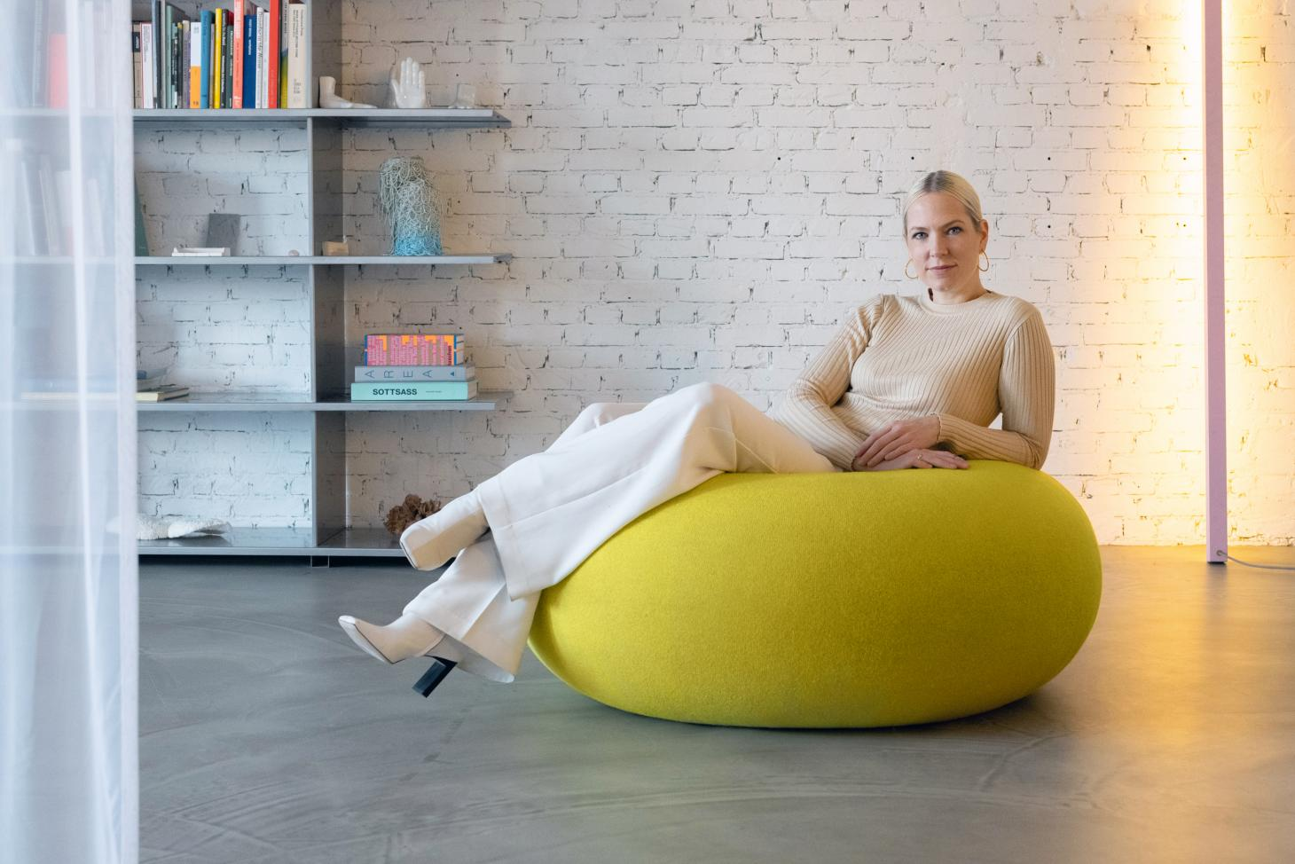 A portrait of Sabine Marcelis sitting on her yellow donut shaped Boa Pouf for Hem at her home in Rotterdam