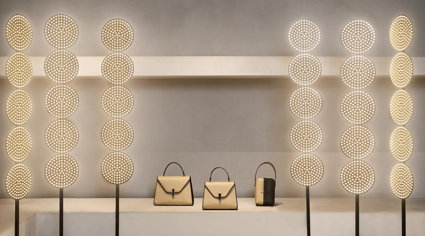 Circular LED lights by Tom Dixon and two-tone bags by Valextra