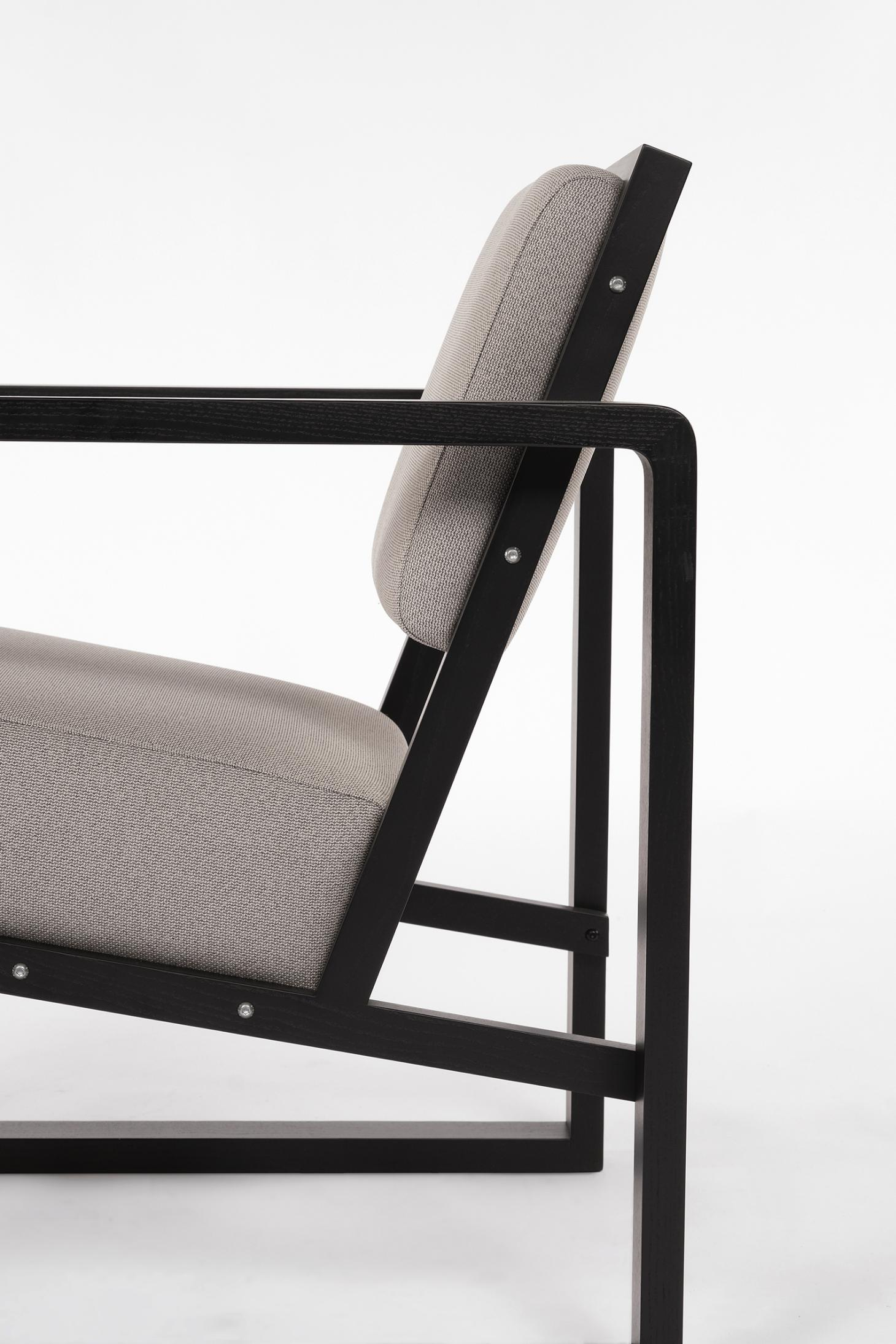 Chair with angular black wooden frame and grey upholstery, shown from the side