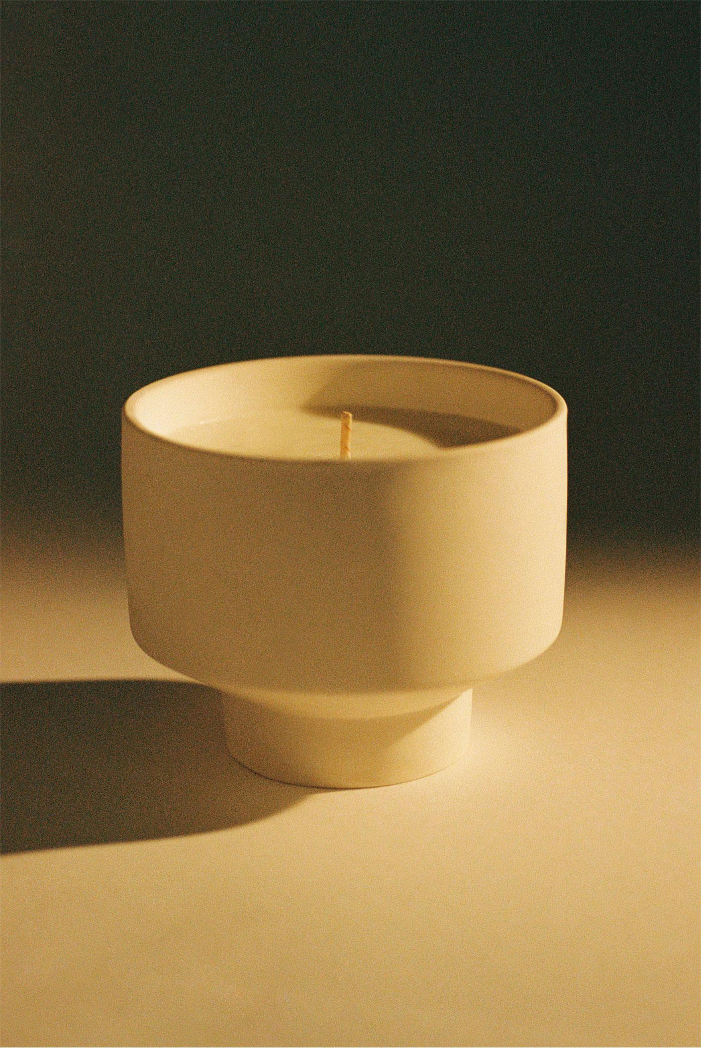 Uniform fragrance candle in white circular holder against black background