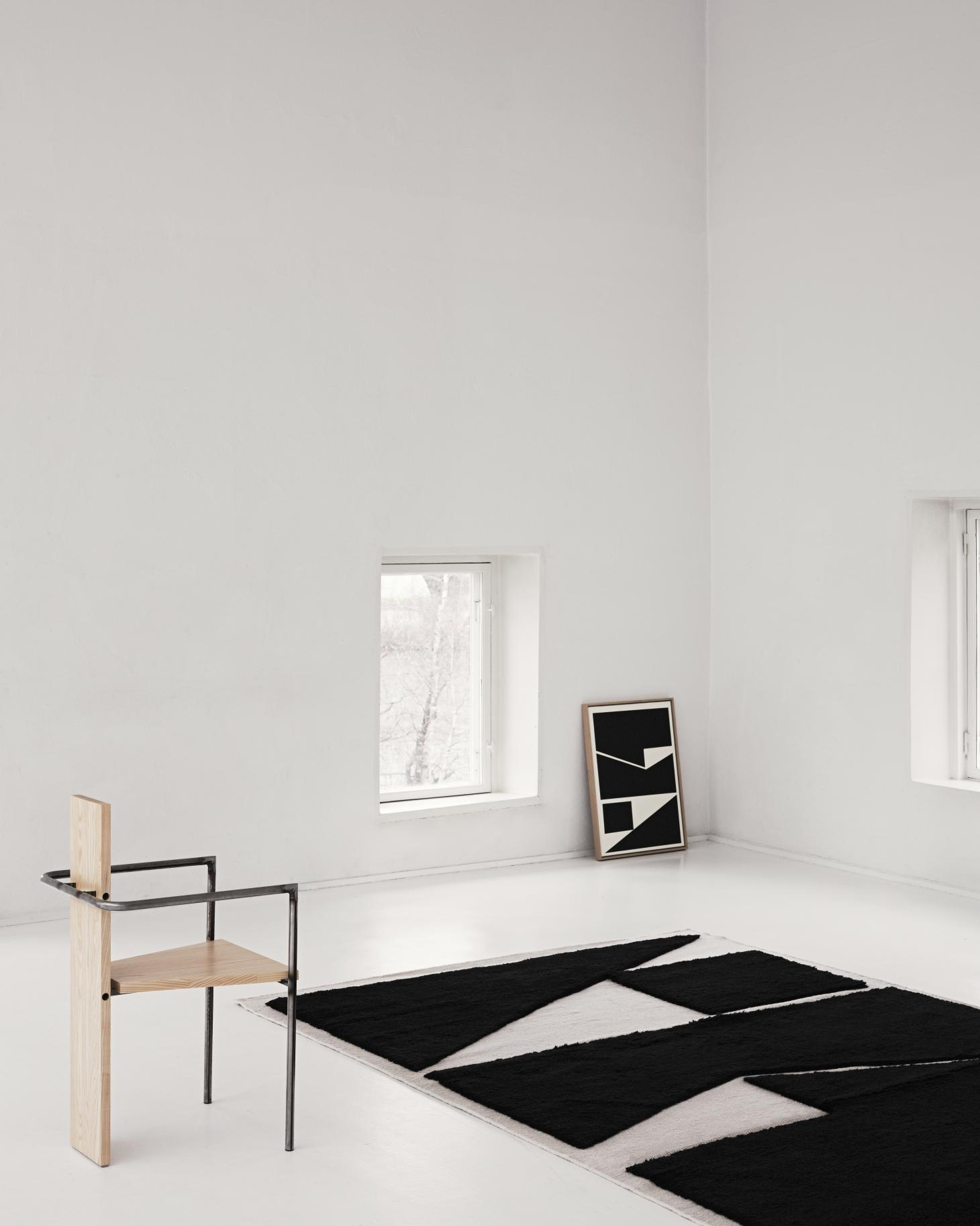 A geometric rug by Nordic Knots pictured in a minimalist white room with wooden furniture