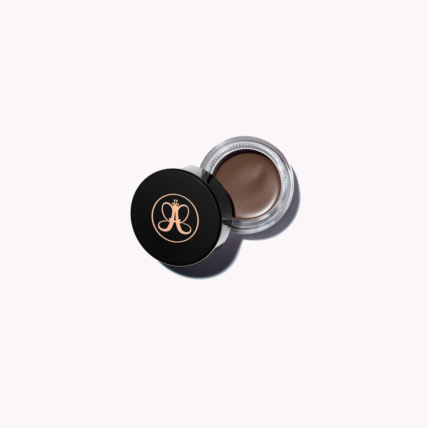 Anastasia Beverly Hills dark brown brow pomade in round glass container against grey background