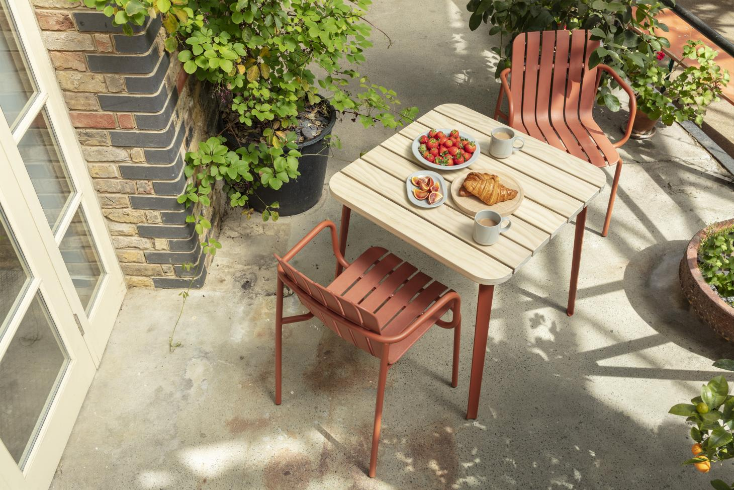 Sustainable outdoor furniture by Very Good and Proper in red, including a chair with recycled and hemp fiber seat and Accoya wood table top
