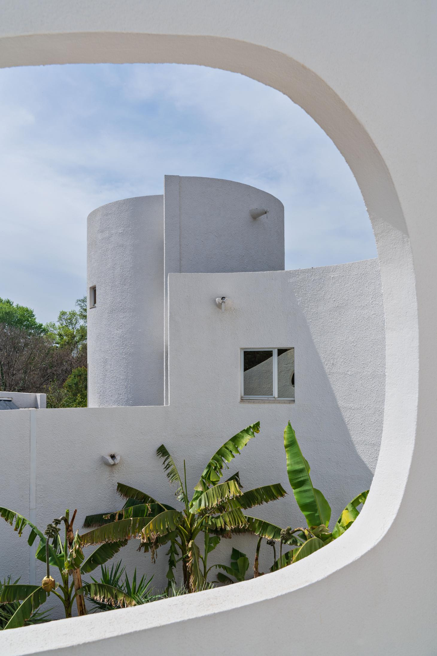 The white modernist architecture of Villa Benkemoun framed by palm trees and blue sky