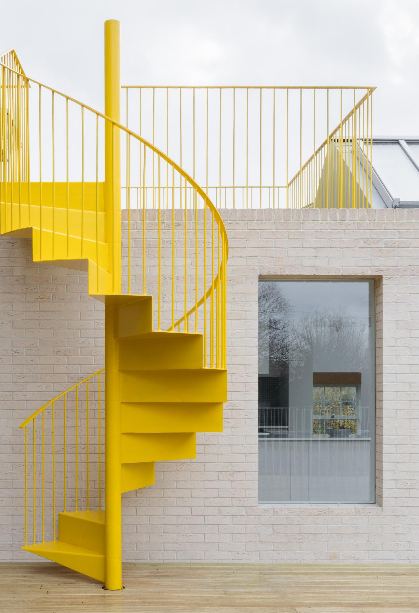 Yellow spiral staircase on apartment terrace