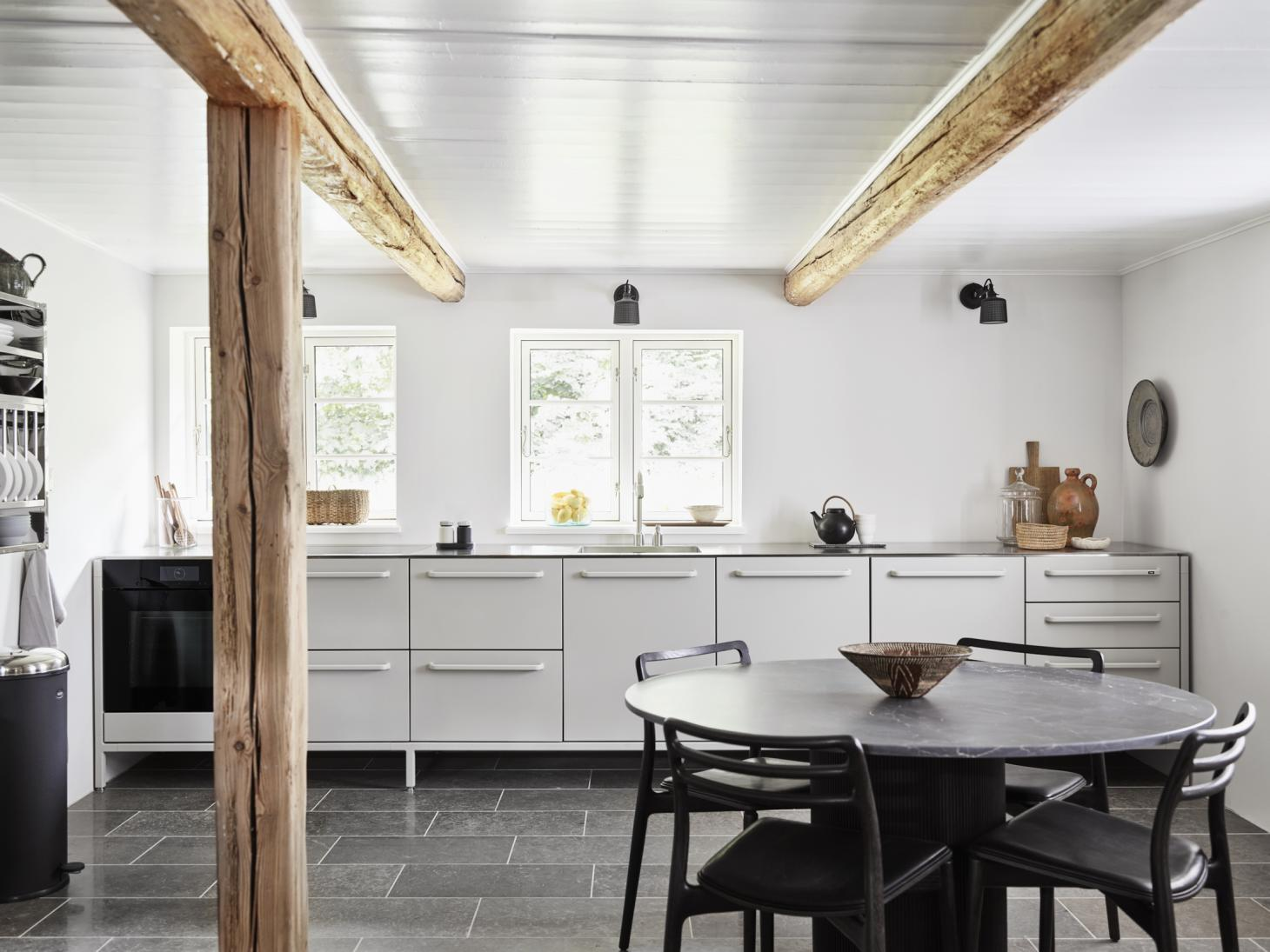 The light-filled kitchen inside the Vipp Farmhouse with a sleek grey aluminium kitchen, round black table and original wooden columns