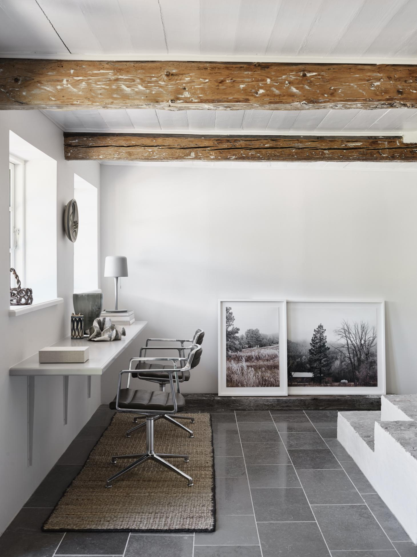 Study in the Vipp Farmhouse with two aluminium office chairs by the window, black and white framed photographs on the floor and visible wooden beams on the ceiling