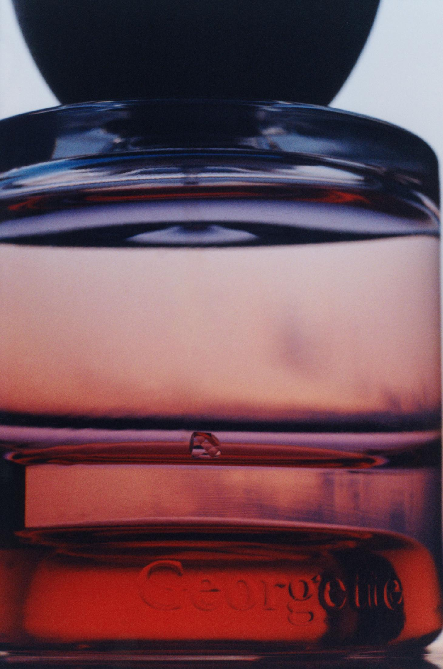 Vyrao Georgette fragrance photographed by Alex Lesse in close up with purple and pink shades running through the bottle