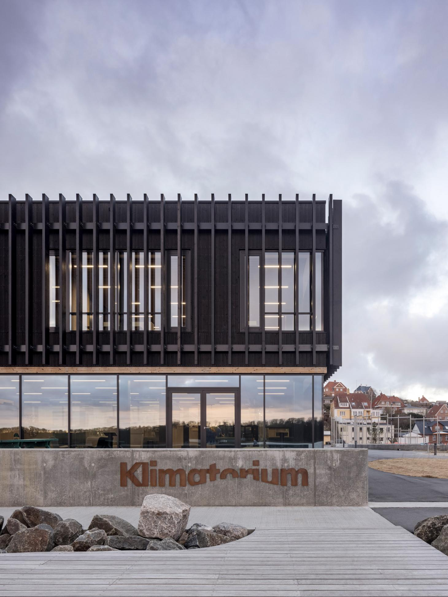 the entrance of the Lemvig Klimatorium is clad in timber as the building sits on a concrete plinth