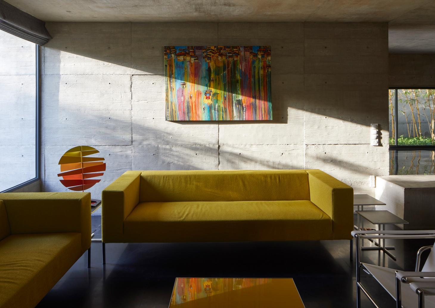 Living room with bright yellow sofa at Surat House by Matharoo Associates in India