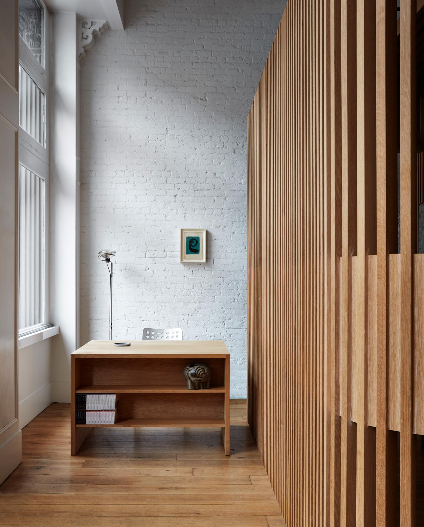A white painted brick wall, a wooden panelled wall and a large window frame the reception space of this Tribeca hair salon with a modernist oak desk