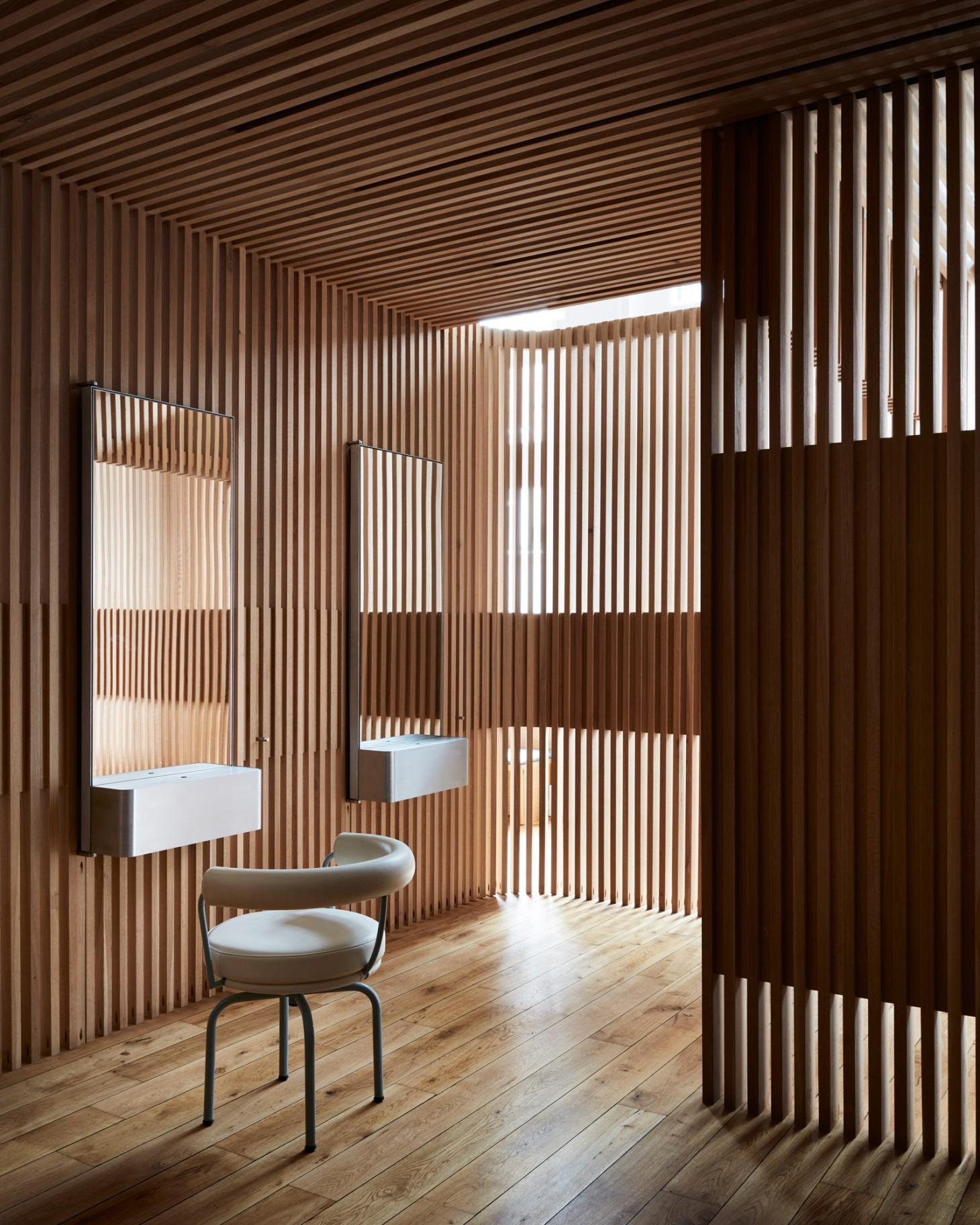 A hair salon interior defined by vertical wood slats with two mirrors and a chair