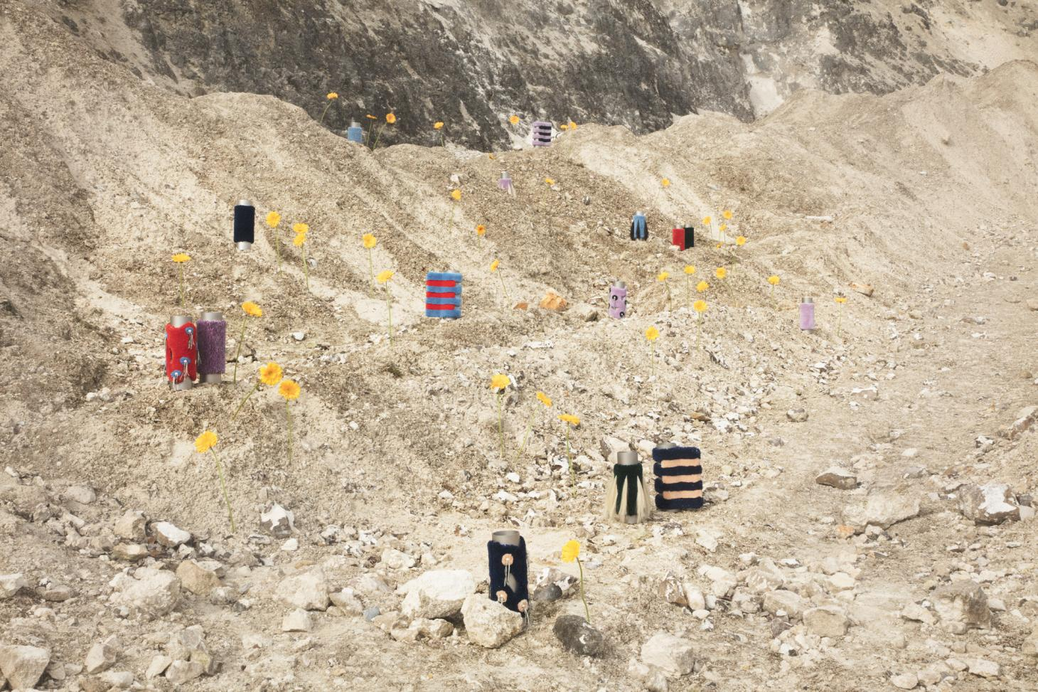 An arrangement of vases and yellow gerberas on a rocky hill by Tableau Copenhagen