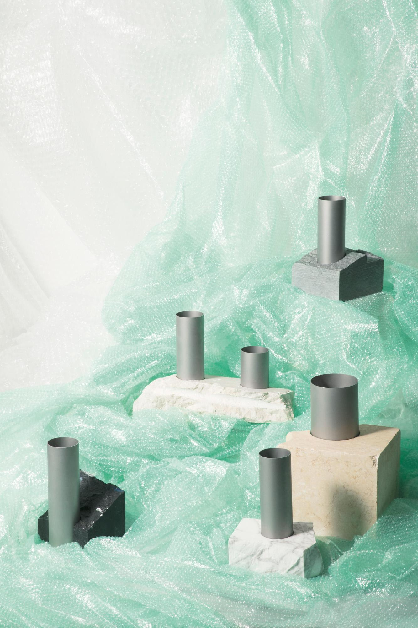 Vases by Tableau Copenhagen andBloc Studios featuring marble bases and tube aluminium tops, shown on teal bubble wrap